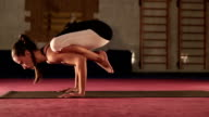 Young flexible Female doing yoga Crane pose video