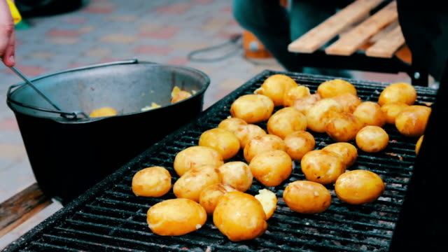 Young fresh potatoes that are laid out and turned over on a barbecue grill on picnic video