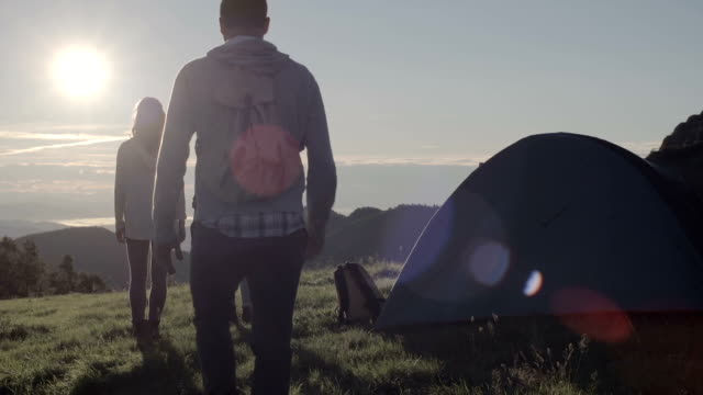 Young friends doing camping looks at sun in mountain outdoor nature scenery during summer sunrise or sunset - HD video footage video