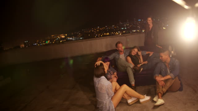 Young friends hanging out on a couch on the rooftop video