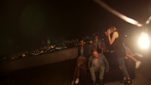 Young friends hanging out on the rooftop for a party video