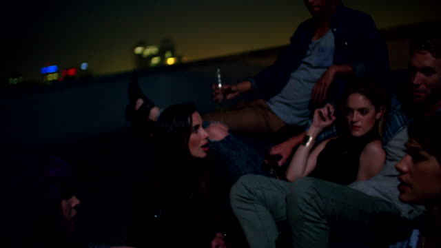 Young friends hanging out with drinks  on the rooftop for a party video
