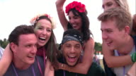 Young friends piggy backing at a music festival, close-up video
