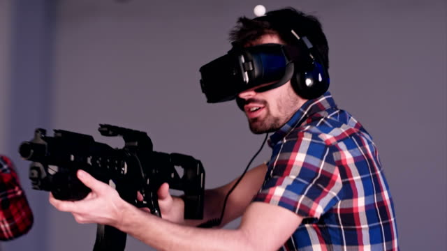 Young friends playing VR sniper game with virtual reality guns and glasses video