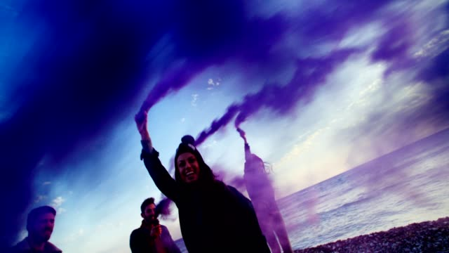 Young friends playing with smoke bombs on a beach video