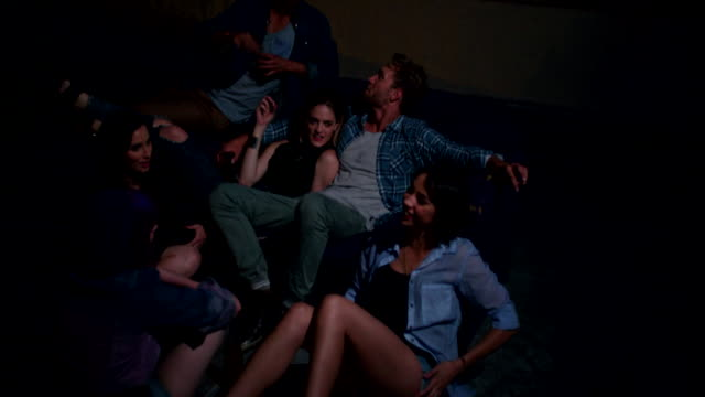 Young friends sitting on a couch on the rooftop for a party video