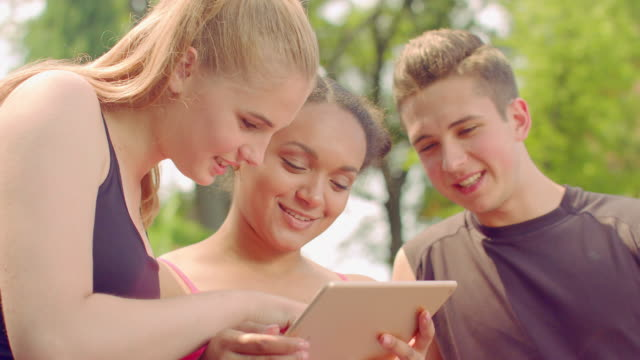 Young friends surfing internet on tablet. Close up of happy people having fun video
