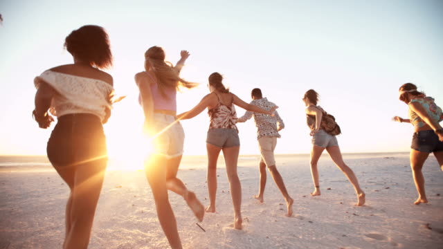 Young friends walking on a beach at sunset video