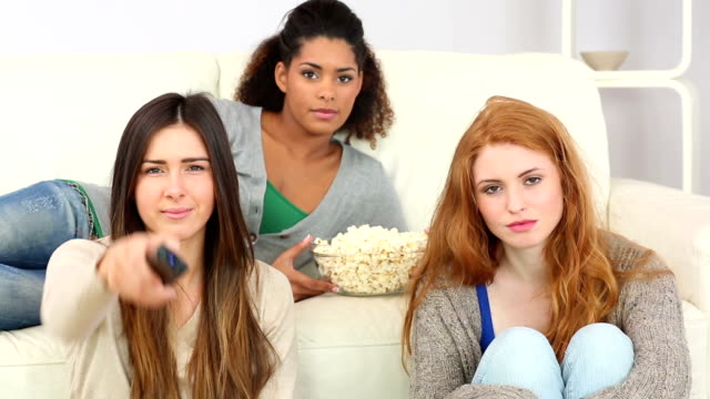 Young friends watching television eating popcorn video