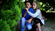 Young girl and boy looking at tree leaves through magnifier video