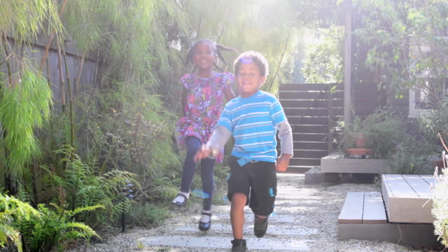 Young girl and boy running and skipping in garden video