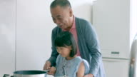 Young girl and her grandfather cooking together video
