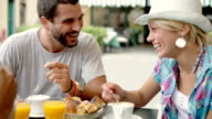 Young girl and man have italian breakfast outdoor CU video