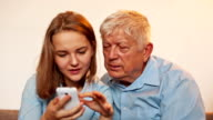 Young Girl and Old Person Learn Smartphone video