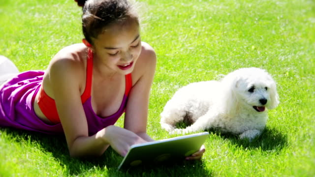 Young girl and pet using tablet video