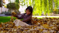 Young girl and puppy playing in fall leaves, slow motion video