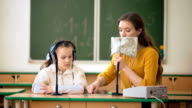 Young girl and teacher using headphones and microphone in the classroom video