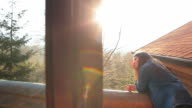 Young girl at the cabin balcony admiring the beautiful view. video