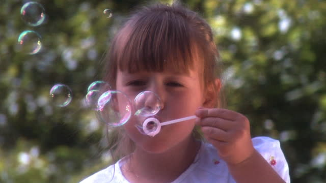 Young girl blowing bubbles video