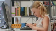 DS Young girl browsing books on library computer video
