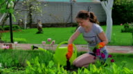 Young girl cares for the lawn near the house video