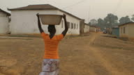 Young girl carrying water on her head in African village video