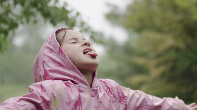 Young girl catching the rain on her tongue video