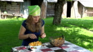young girl clean forest chanterelle at table village yard. FullHD video