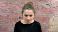 Young girl depict repentance. Someone scold her. Casting. Brick wall background video