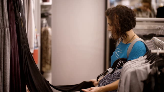 A young girl dressed in a blue T-shirt and gray backpack on the back to choose between gray, violet and black jumpsuit in a clothing store, holding a few blouses video