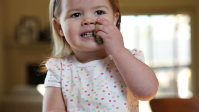 Young girl eating broccoli video