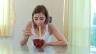 Young girl eating ramen noodles video