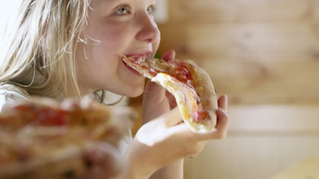 MS Young girl eating slice of pizza video