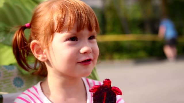 A young girl eats a lollipop outdoor video