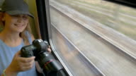 Young girl going by train and taking pictures video