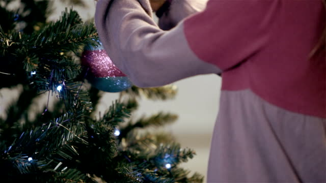 Young girl hanging Christmas decorations video