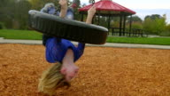 Young girl hangs from underneath a tire swing video