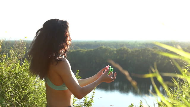 Young girl having fun outdoors with Spinner, slow motion video