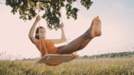Young girl having fun swinging on a tree swing video
