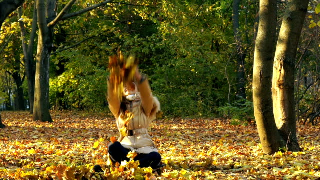 Young Girl Having Fun Throwing Yellow Leaves. video