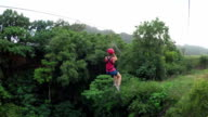 Young girl having fun while riding zipline cable above beautiful green jungle video