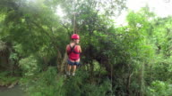 Young girl having fun while riding zipline cable forth and back video