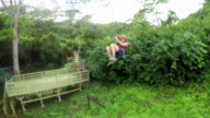 Young girl having fun while riding zipline cable upside down video