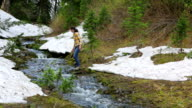 Young girl hikes along alpine stream video