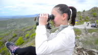 young girl hiking and trekking on mountain peak with binoculars video