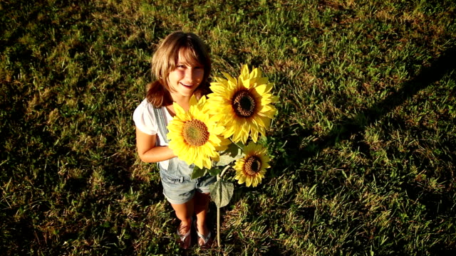 Young girl holding a sunflower at sunset and looking up video