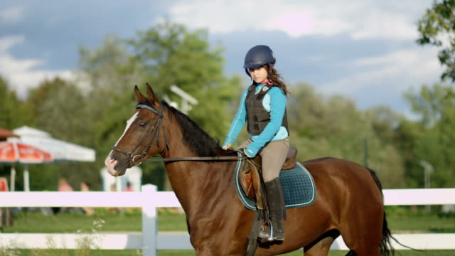 SLOW MOTION Young girl horseback riding beautiful brown mare in outdoor arena video