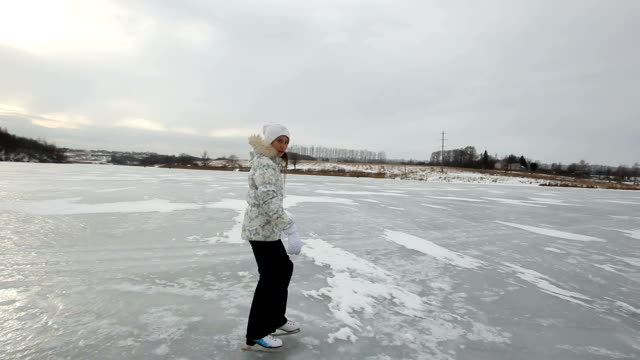 Young girl ice skating on frozen lake video