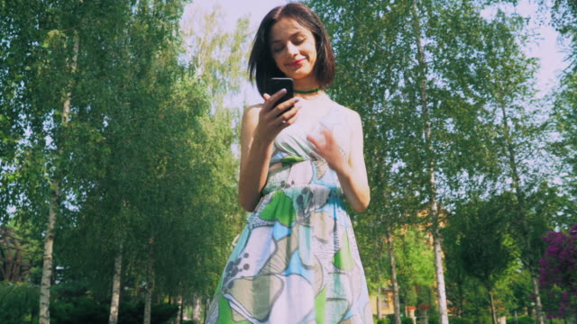 Young girl in a bright dress is in the park, reading a message on your phone and smiles video