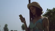 A young girl in a hat gaining a message on the phone video